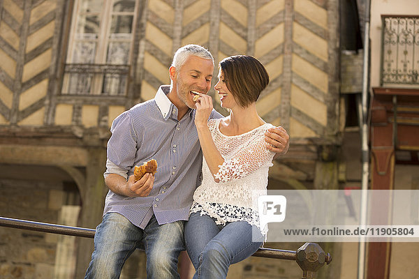 Caucasian couple eating bread on railing