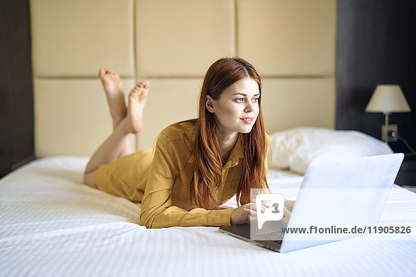 Caucasian woman laying on bed using laptop
