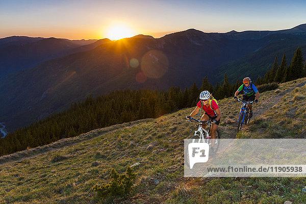 Caucasian couple mountain biking on trail