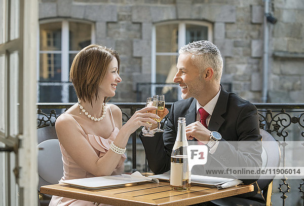 Well-dressed Caucasian couple toasting with champagne