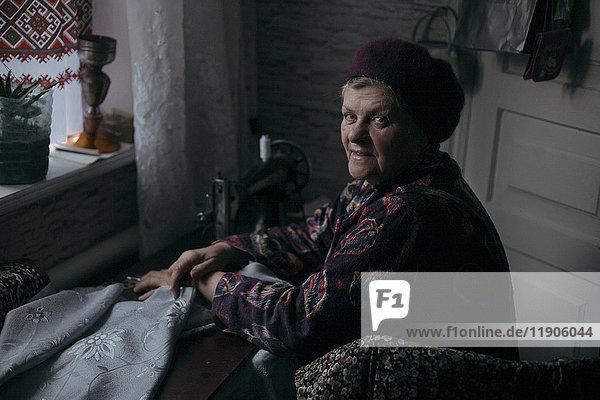 Older Caucasian woman using sewing machine