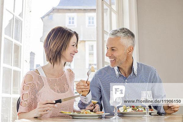 Caucasian couple eating salad in restaurant