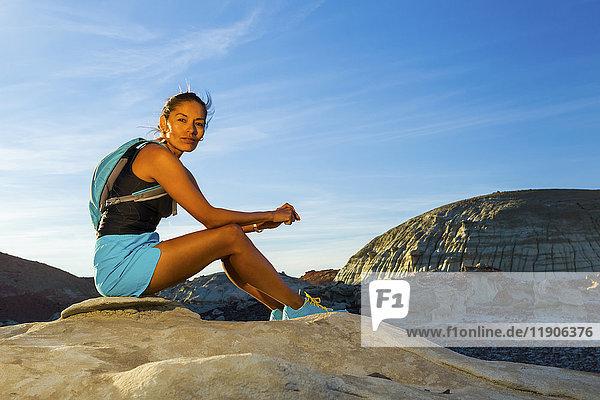 Native American woman sitting on rock in desert