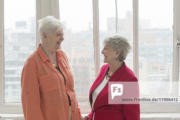 Older Caucasian women laughing near window