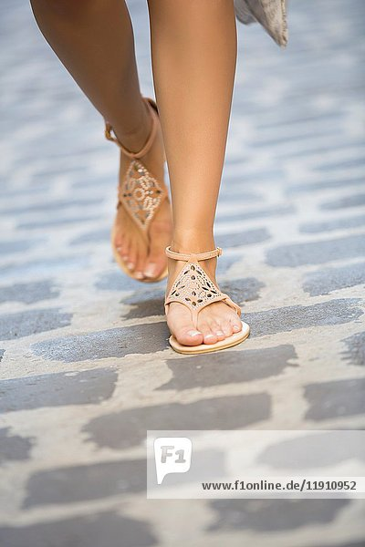 Woman wearing sandals walking on cobbled road.