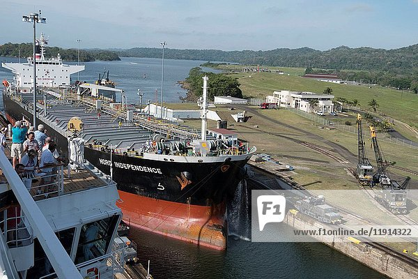 Tourists watch as ships pass through one of the locks at the Panama Canal.