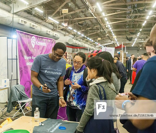 Workers from Voux speak to attendees at the TechDay New York event on Tuesday  April 18  2017. Thousands attended to seek jobs with the startups and to network with their peers. TechDay bills itself as the U. S. 's largest startup event with over 500 exhibitors.