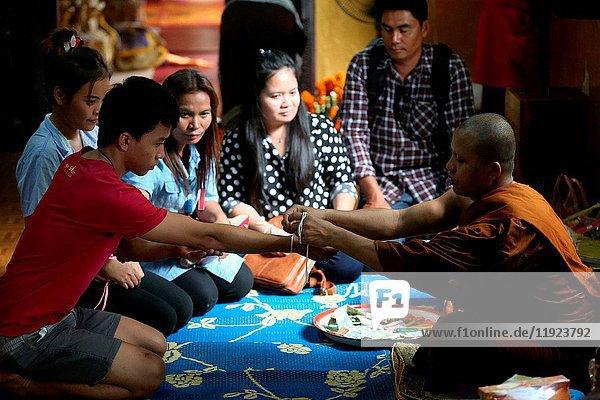 Monk ties blessed cotton bracetet (Sai-sin) around a wrist.