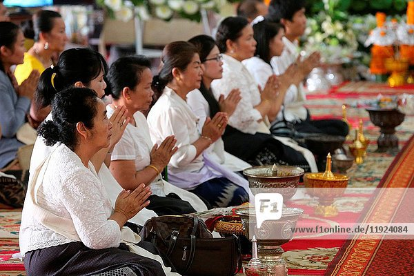 Seated women chanting and reading prayers at a ceremony.