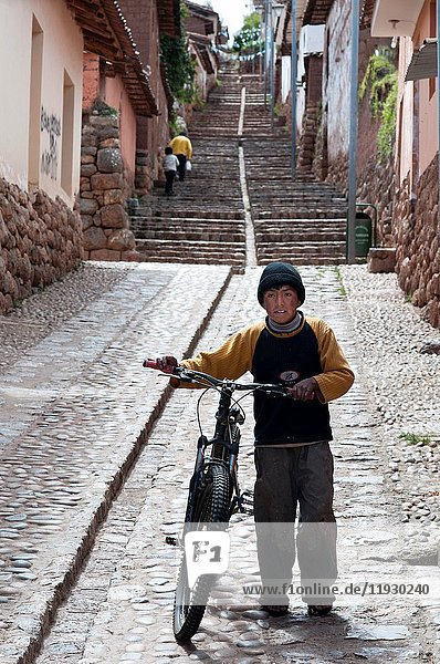 A child on a bicycle in one of the steep streets of the small village of Chinchero in the Sacred Valley near Cuzco. Chinchero is a small Andean Indian village located high up on the windswept plains of Anta at 3762m about 30km from Cusco. There are beautiful views overlooking the Sacred Valley of the Incas  with the Cordillera Vilcabamba and the snow-capped peak of Salkantay dominating the western horizon. Chinchero is believed to be the mythical birthplace of the rainbow. Its major claim to tourism is its colourful Sunday market which is much less tourist-orientated than the market at Pisac.The village mainly comprises mud brick (adobe) houses  and locals still go about their business in traditional dress.The village may have been an important town in Inca times. The most striking remnant of this period is the massive stone wall in the main plaza which has ten trapezoidal niches. The construction of the wall and many other ruins and agricultural terraces (which are still in use) are attributed to Inca Tupac Yupanqui who possibly used Chinchero as a kind of country resort. Entrance to the main plaza and ruins requires a 'boleto turistico'.In the main plaza an adobe colonial church  dating from the early seventeenth century  has been built upon the foundations of an Inca temple or palace. The ceiling and walls are covered in beautiful floral and religious designs. The church is open on Sundays for mass.Half an hour's walk from the village brings you to Lake Piuri which once fed Cusco with water. It takes about 3 hours to walk around the lake passing through small picturesque villages.