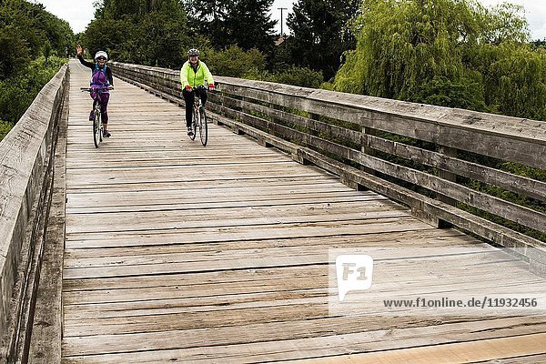 Two middle-aged women bicycle on a wooden bridge in Victoria  BC  Canada