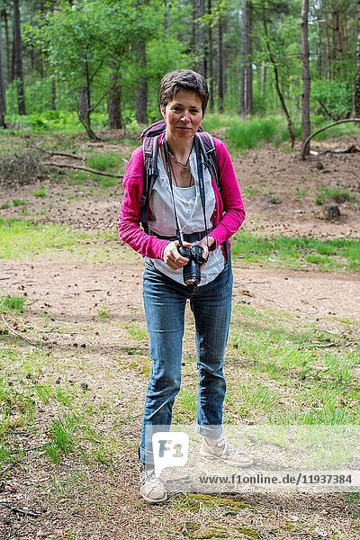 Esbeek  Netherlands. Mature adult woman strolling through a forest on a sunday afternoon.