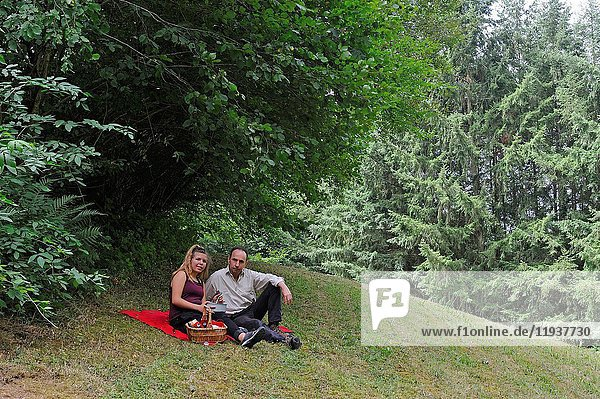 Father and daughter having pic-nic in a meadow  Puy-de-Dome department  Auvergne-Rhone-Alpes region  France  Europe.