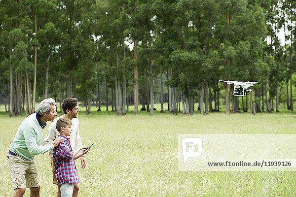 Junge fliegende Fernsteuerungsdrohne im offenen Feld,  während Vater und Großvater zusehen.