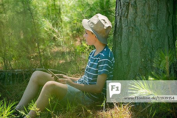 Junge lehnt an Baumstamm mit digitalem Tablett in der Hand