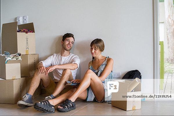 Junges Paar in neuem Haus  umgeben von Pappkartons