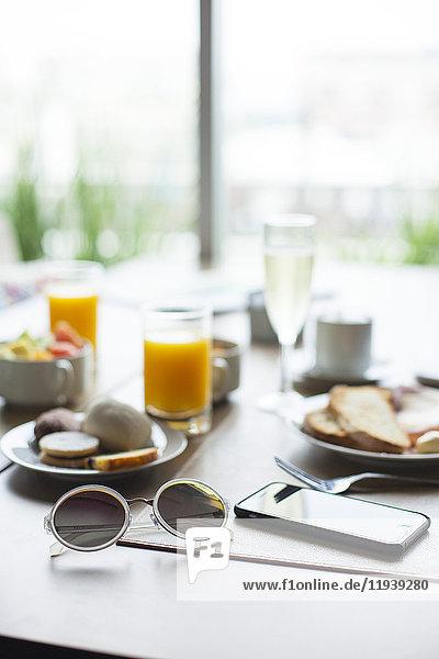Sonnenbrille und Smartphone auf dem Frühstückstisch im Cafe