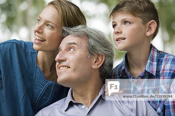 Familie lächelt zusammen und schaut weg  Porträt