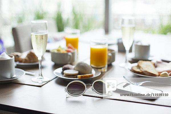 Sonnenbrille und Frühstück auf dem Tisch im Cafe