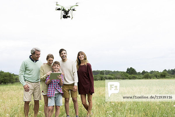Mehrgenerationen-Familie spielt mit Drohne im Feld