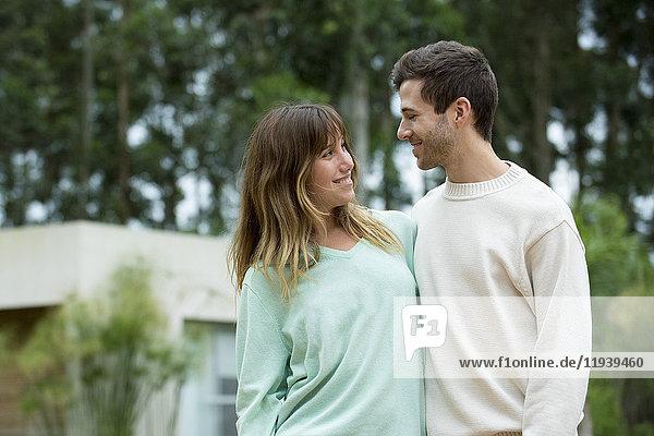Junges Paar lächelt sich im Freien an.