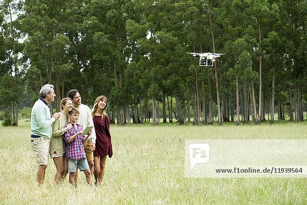 Junge bedient ferngesteuerte Drohne  während Eltern und Großeltern zusehen.