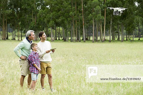 Mann fliegt ferngesteuerte Drohne im offenen Feld  während ältere Männer und Jungen zusehen.
