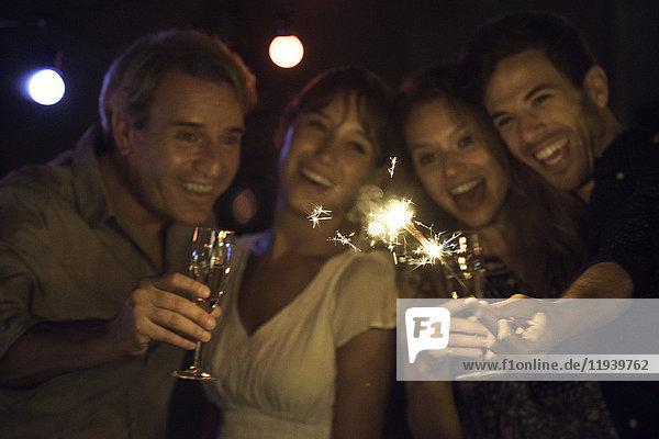 Freunde feiern mit Wunderkerzen und Champagner