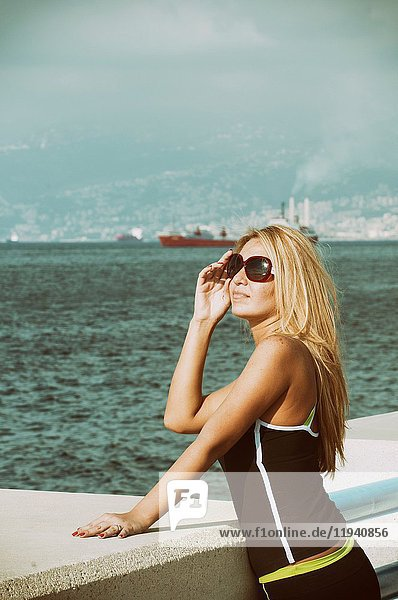 Beautiful blond woman wearing sunglasss standing by the sea looking away.