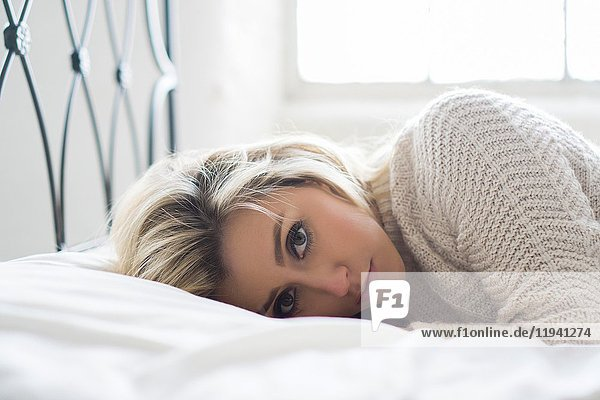 Beautiful young blond woman laying down in bed.