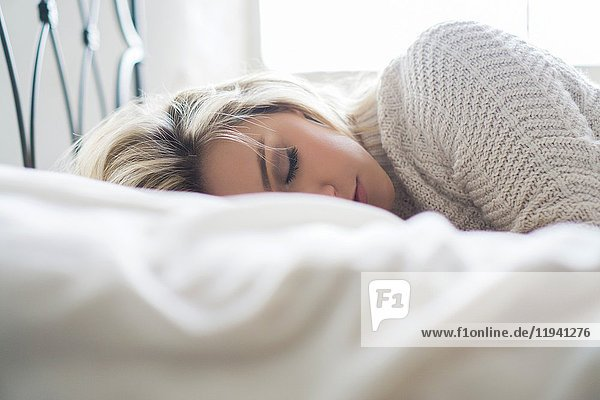 Young blond woman sleeping in bed.