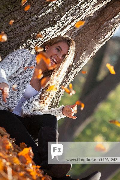 Glückliche junge Frau im Freien im Herbst