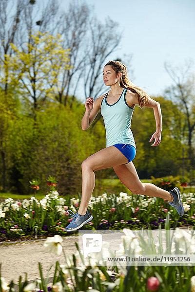 Sportliche Frau beim Laufen im Park im Frühling