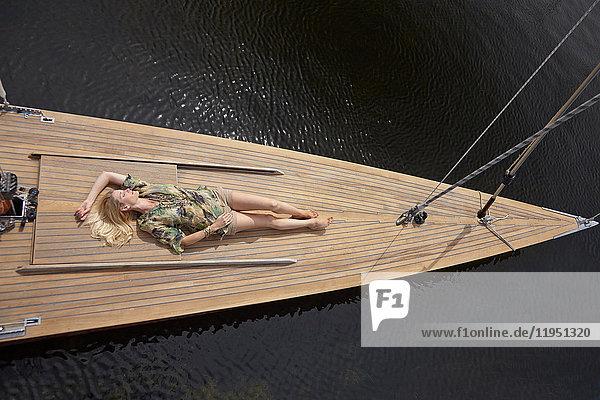 Deutschland  Bayern  Starnberger See  Frau liegt auf dem Deck eines Segelboots