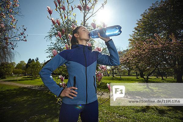 Sportliche Frau trinkt Wasser im Park im Frühling