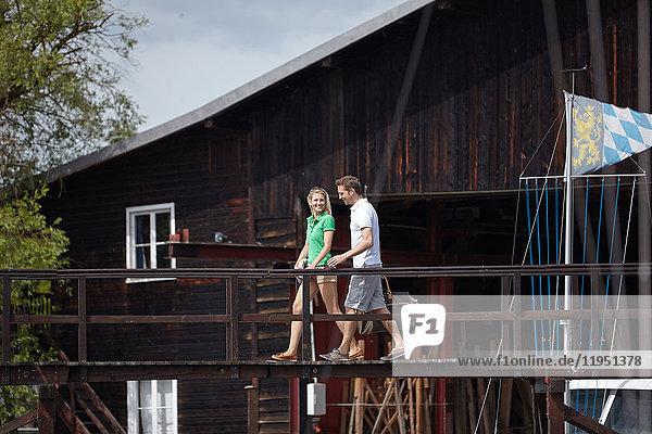 Deutschland  Bayern  Starnberger See  Paar geht an einem Bootshaus