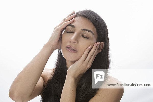 Dunkelhaarige Frau hält ihren Kopf in den Händen