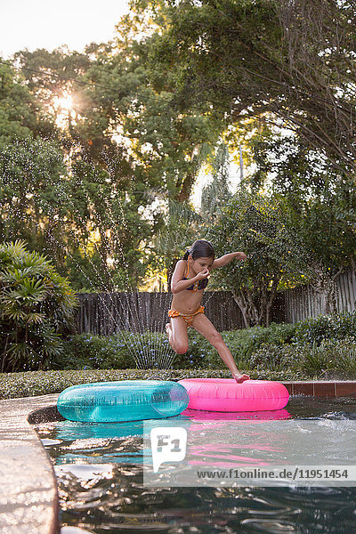 Young girl jumping into outdoor swimming pool  mid-air