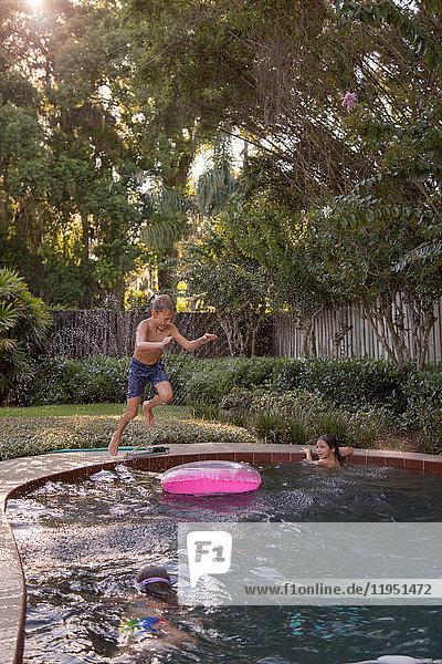 Kinder schwimmen im Gartenpool  ein Junge springt hinein  in der Luft