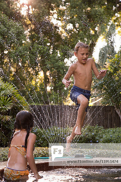 Young boy jumping into garden pool  mid-air