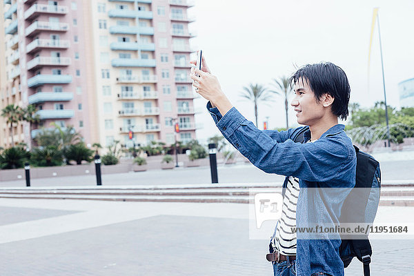 Young man outdoors  taking picture using smartphone