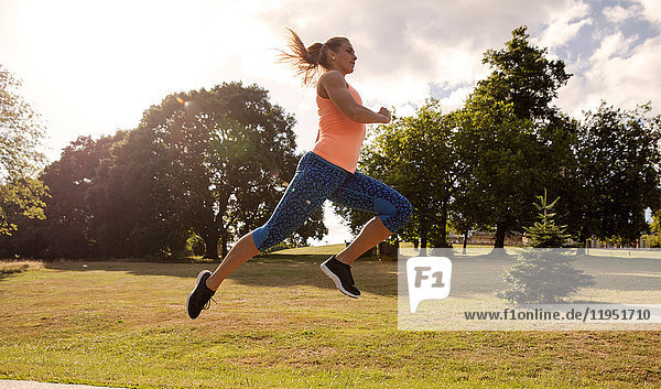 Young woman training in park  leaping mid air