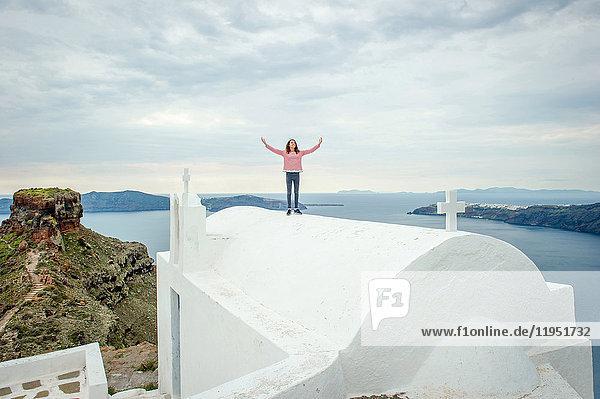 Mädchen oben auf der Kirche stehend  Oía  Santorini  Kikladhes  Griechenland