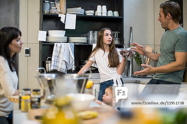 Ehemann und Ehefrau sprechen mit Tochter in der Küche  Kleinkind greift nach Zitronen