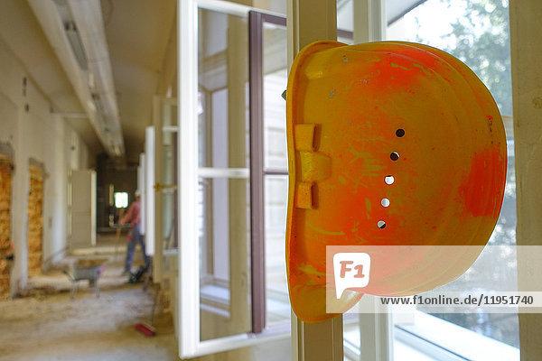 Bauarbeiterhelm an Fensterrahmen