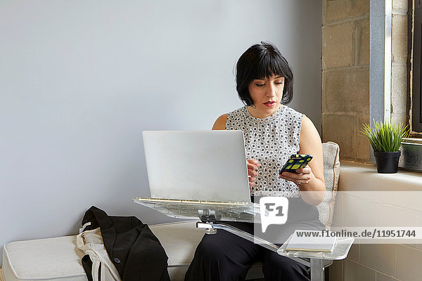 Woman sitting using laptop on laptop stand  holding smartphone
