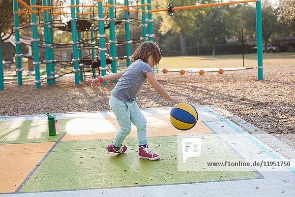 Mädchen hüpft Basketball auf dem Spielplatz