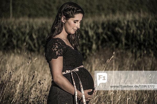 Schwangere Frau auf einem Feld