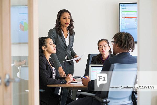 Geschäftsmann und Geschäftsfrauen sitzen im Büro und diskutieren