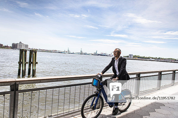 Mid adult businessman cycling along city river waterfront